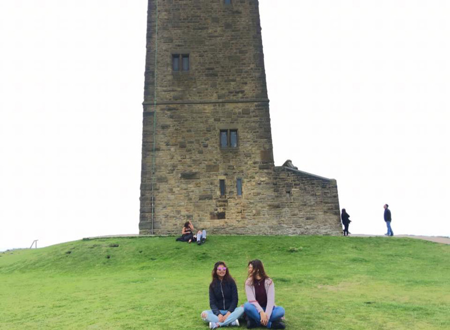 Two students sitting on grass in front of castle hill.