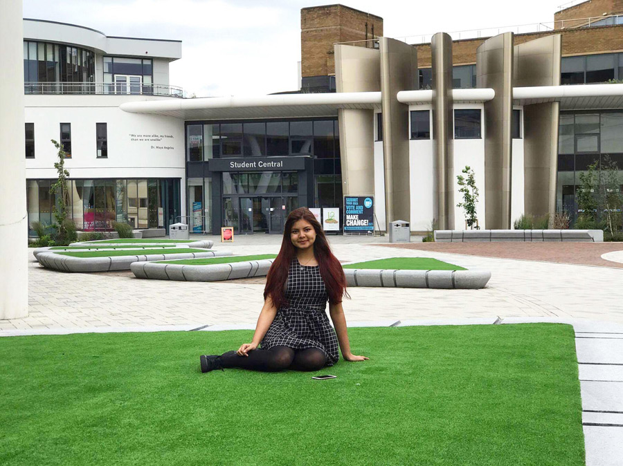 A photo of Sanjida sitting on grass on The University Campus plaza.