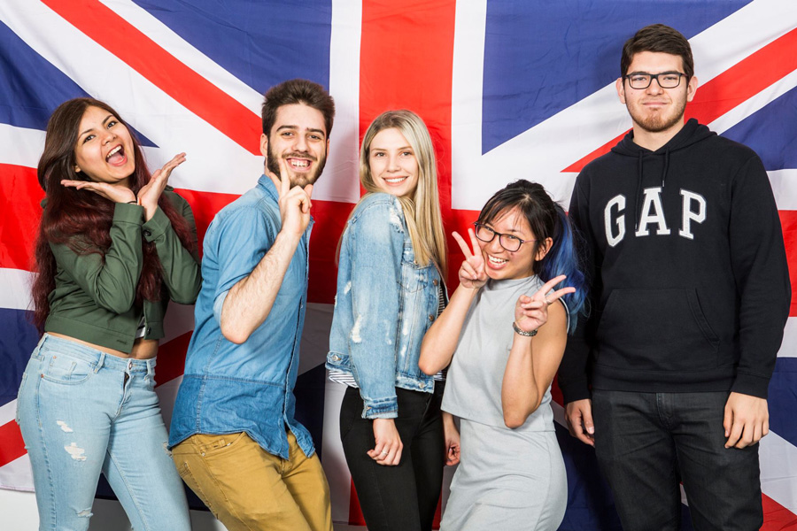 Five students posing in front of a Union Jack.